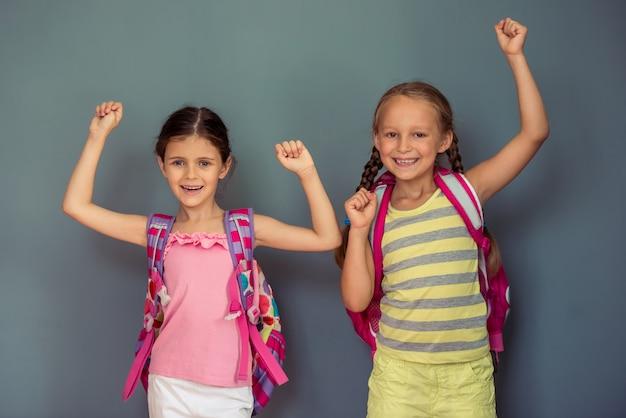 Due bambine sveglie con i sacchetti di scuola stanno esaminando la macchina fotografica