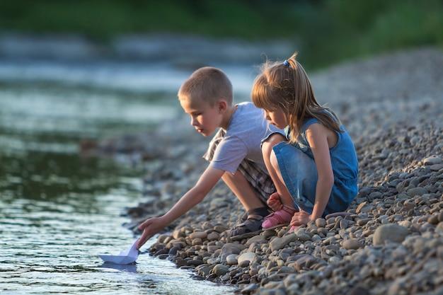 Due bambini biondi svegli, ragazzo e ragazza sulla sponda del fiume che inviano le barche del libro bianco dell'acqua. gioie e giochi di infanzia felice e concetto di attività all'aperto.