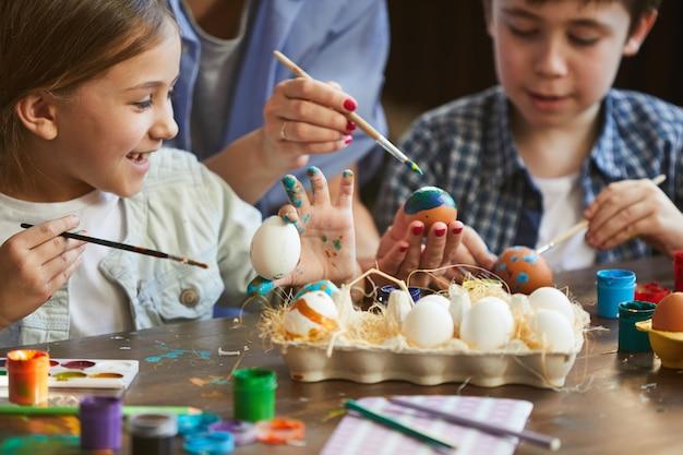 Due bambini che dipingono le uova di pasqua