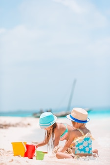 Due bambini che fanno il castello di sabbia e divertirsi in spiaggia tropicale