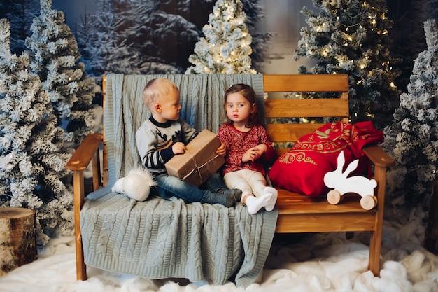 Due bambini che giocano con il natale si avvicinano alla decorazione e all'albero di natale