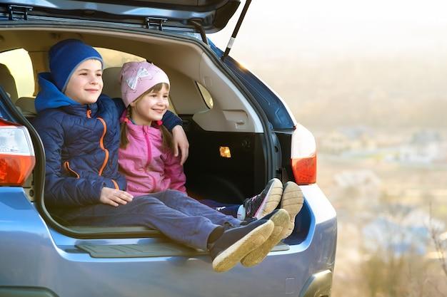 Due bambini felici ragazzo e ragazza che si siedono insieme in un bagagliaio. fratello allegro e sorella che si abbracciano nel compartimento bagagli del veicolo della famiglia.