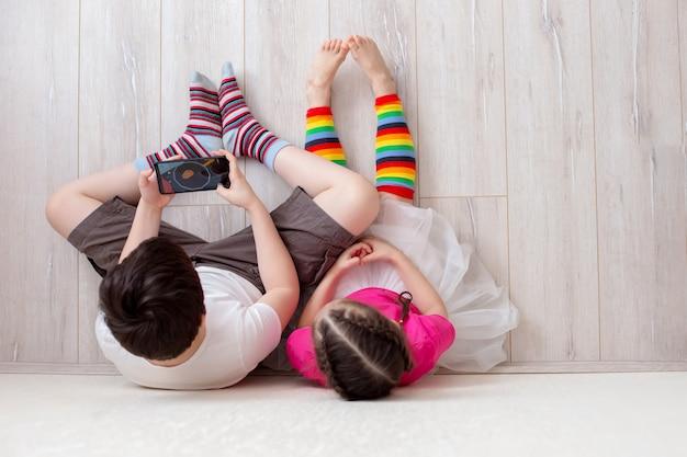 Due bambini, fratello e sorella, sono seduti sul pavimento e giocano su uno smartphone