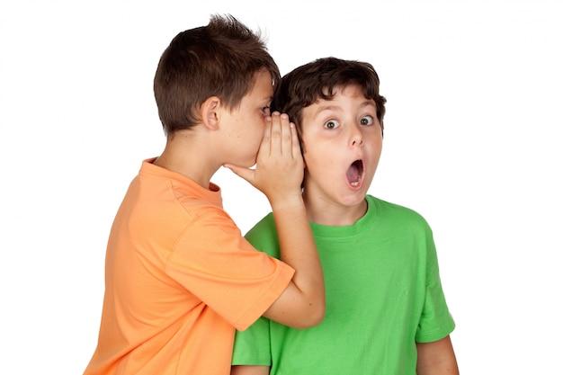 Due bambini hanno detto il gossip isolato su sfondo bianco