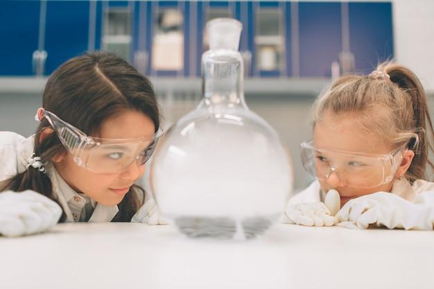 Due bambini in laboratorio ricoprono l'apprendimento della chimica nel laboratorio della scuola. giovani scienziati in occhiali protettivi che fanno esperimento in laboratorio o gabinetto chimico. studiare ingredienti per esperimenti.