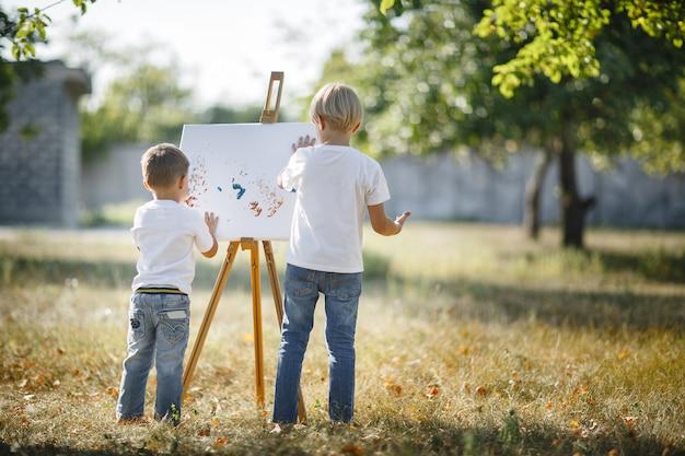 Due bambini irriconoscibili che disegnano all'aperto
