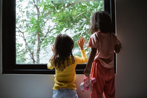 Due bambini piccoli che vedono dalla finestra