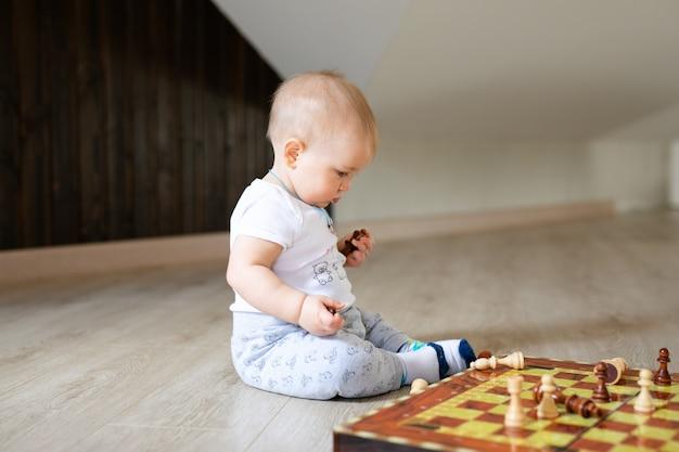 Due bambini ragazzo e ragazza che giocano a scacchi sul pavimento di legno bianco a casa.
