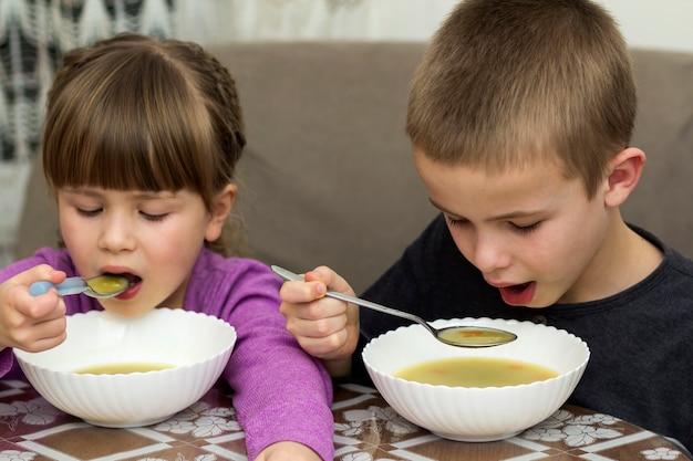 Due bambini ragazzo e ragazza che mangiano minestra