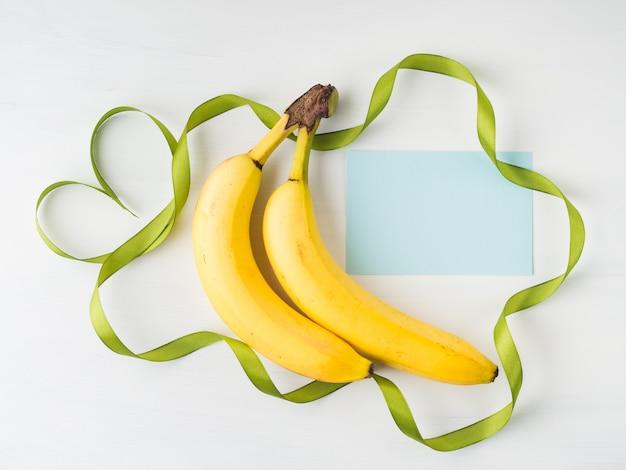Due banane con cornice di nastro verde e simbolo del cuore su bianco