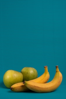 Due banane e due mele verdi su uno sfondo blu chiaro.