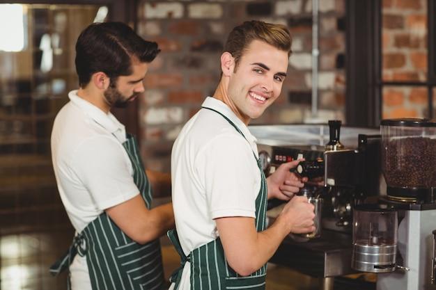 Due baristi sorridenti che preparano il caffè