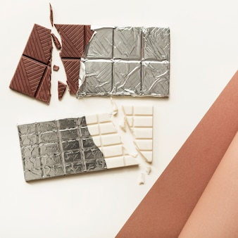 Due barrette di cioccolato in foglia d'argento su sfondo bianco
