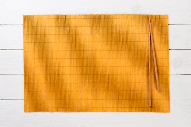 Due bastoncini dei sushi con la stuoia di bambù gialla vuota o il piatto di legno sulla vista superiore di legno bianca con copyspace. cibo asiatico vuoto