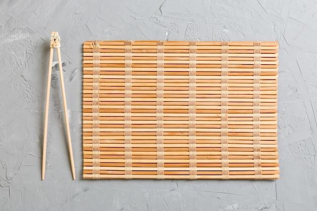 Due bastoncini per sushi con stuoia di bambù vuota o piatto di legno su pietra