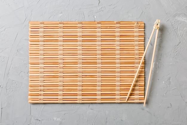 Due bastoncini per sushi con tappetino di bambù vuoto