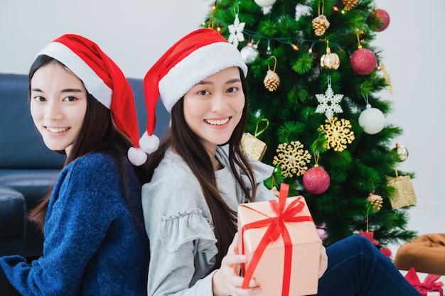 Due bei contenitori di regalo asiatici della tenuta della donna. fronte sorridente nella sala con la decorazione dell'albero di natale per le vacanze