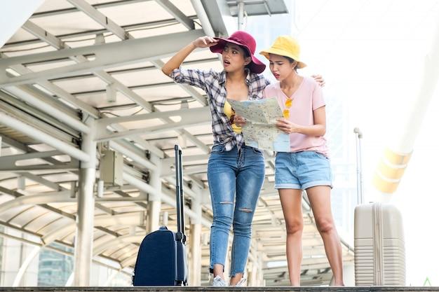 Due bei giovani viaggiatori che vagano nella città visualizzazione della mappa per vedere le direzioni