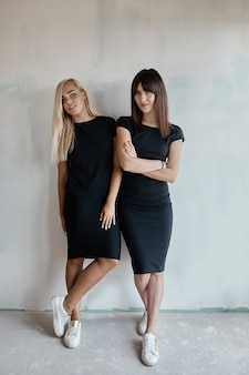 Due bella donna in un abito nero al coperto