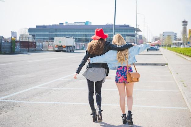 Due bella ragazza bionda e bruna divertirsi in città