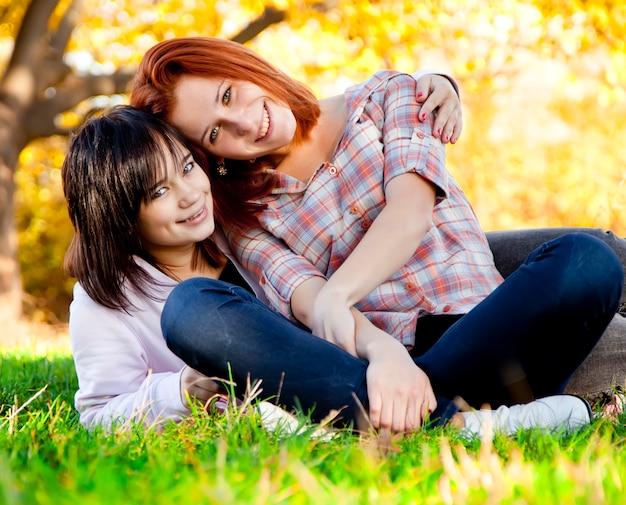 Due bella ragazza teenager all'erba verde nel parco.