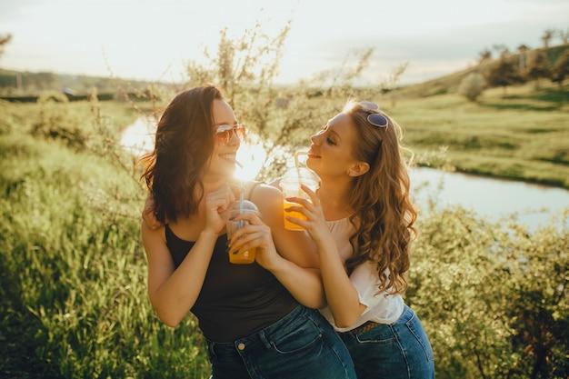 Due belle amiche stanno bevendo un cocktail con la paglia, si divertono al tramonto, espressione facciale positiva, all'aperto