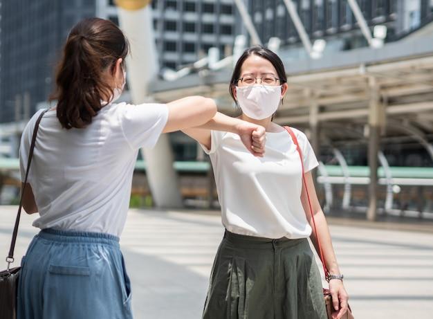 Due belle donne asiatiche si salutano con il gomito, indossando una maschera medica monouso