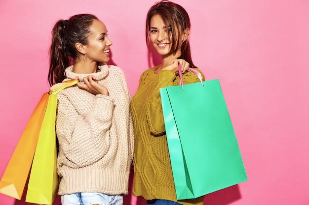 Due belle donne bellissime sorridenti. donne che stanno in maglioni bianchi e verdi alla moda che tengono i sacchetti della spesa, sulla parete rosa.