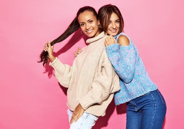 Due belle donne bellissime sorridenti. donne in piedi in eleganti maglioni bianchi e blu, sul muro rosa.
