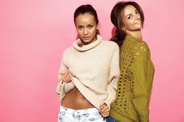 Due belle donne bellissime sorridenti. donne in piedi in eleganti maglioni bianchi e verdi, sul muro rosa.
