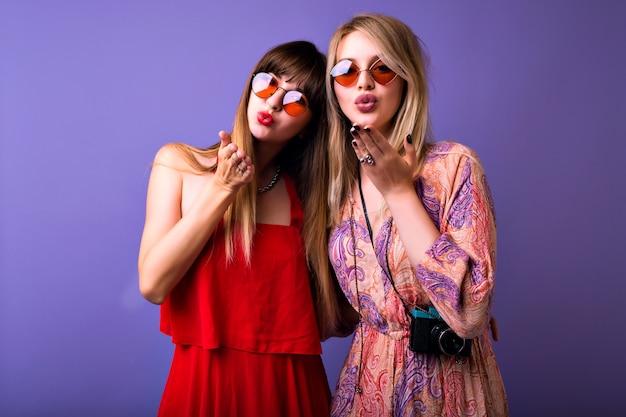 Due belle donne bionde e mora ti stanno mandando un bacio d'aria, spazio viola da studio, abiti vintage eleganti e occhiali da sole boho.