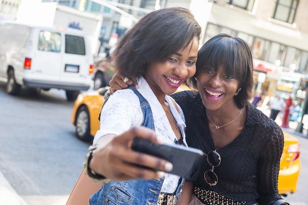 Due belle donne di colore prendendo selfie a new york