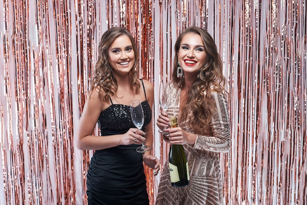Due belle donne eleganti che bevono champagne contro la decorazione scintillante