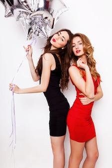 Due belle donne eleganti con labbra rosse in serata vestito nero e rosso divertendosi. uno che tiene le stelle d'argento palloncini in mano e sorride.