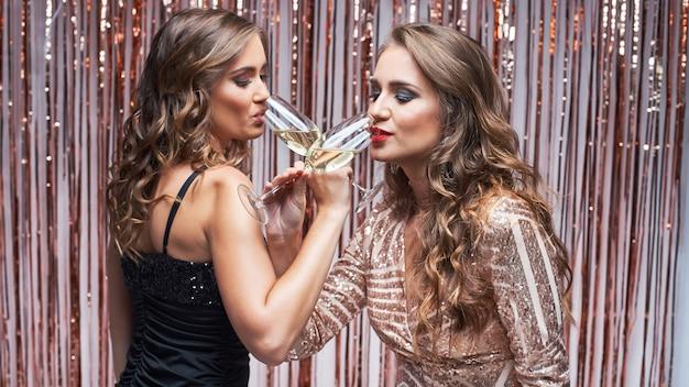 Due belle donne eleganti in abiti da sera bevendo champagne.