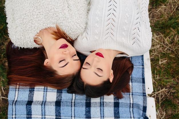 Due belle donne giacciono sulla panchina e guardano