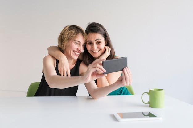 Due belle donne in ufficio prendendo un selfie con il cellulare. sfondo bianco. concetto di ufficio moderno