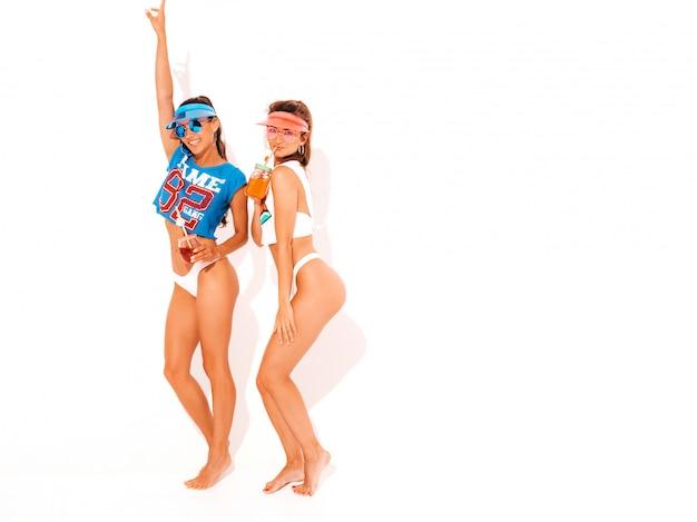 Due belle donne sexy sorridenti in mutande ed argomento bianchi di estate. ragazze alla moda in occhiali da sole, visiera trasparente. impazzendo. modelli divertenti isolati. bere cocktail fresco bevanda liscia