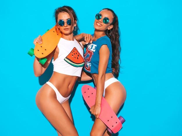 Due belle donne sexy sorridenti nelle mutande e nell'argomento di estate. ragazze alla moda in occhiali da sole. modelle positive che si divertono con colorati penny skateboard. isolato