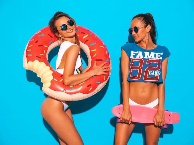 Due belle donne sexy sorridenti nelle mutande e nell'argomento di estate. ragazze in occhiali da sole. modelle positive che si divertono con colorati penny skateboard. con ciambella lilo materasso gonfiabile