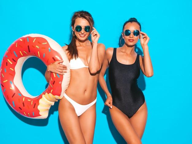 Due belle donne sorridenti sexy in costume da bagno bianco e nero estate costumi da bagno. ragazza in occhiali da sole. modelli positivi che si divertono con il materasso gonfiabile di ciambella lilo. isolato sulla parete blu