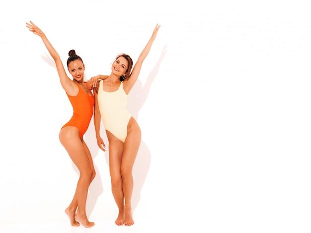 Due belle donne sorridenti sexy in costume da bagno rosso e giallo colorato estate costumi da bagno. divertimento con i modelli alla moda. ragazze isolate alzando le mani. lunghezza intera
