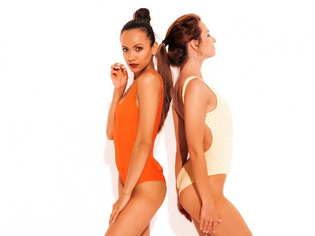 Due belle donne sorridenti sexy in costume da bagno rosso e giallo colorato estate costumi da bagno. divertimento con i modelli alla moda. ragazze isolate