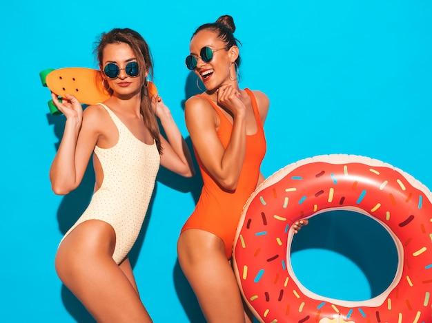 Due belle donne sorridenti sexy in costumi da bagno colorati costumi da bagno estate. ragazze in occhiali da sole. modelle positive che si divertono con colorati penny skateboard. con ciambella lilo materasso gonfiabile