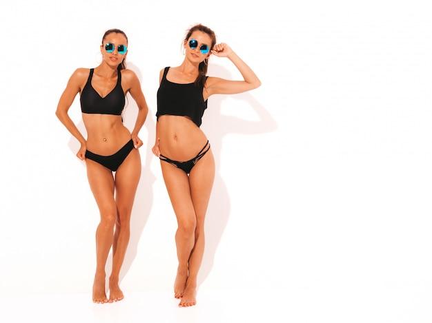 Due belle donne sorridenti sexy in lingerie nera. divertimento con i modelli alla moda. ragazze isolate in occhiali da sole. lunghezza intera