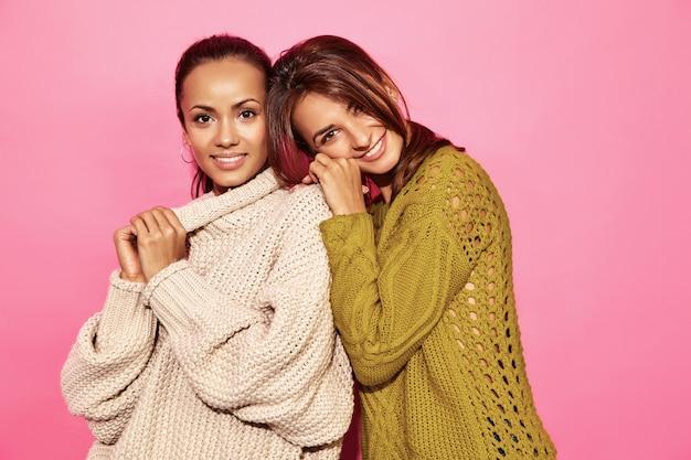 Due belle donne splendide sorridenti sexy. donne calde che stanno e che abbracciano in maglioni bianchi e verdi alla moda, sulla parete rosa.