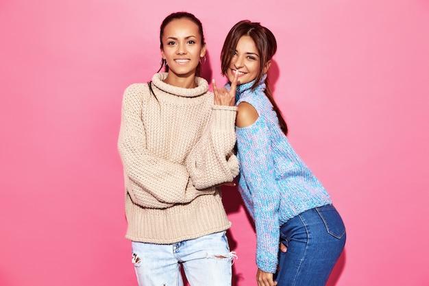 Due belle donne splendide sorridenti sexy. donne calde in piedi in eleganti maglioni bianchi e blu, sulla parete rosa.