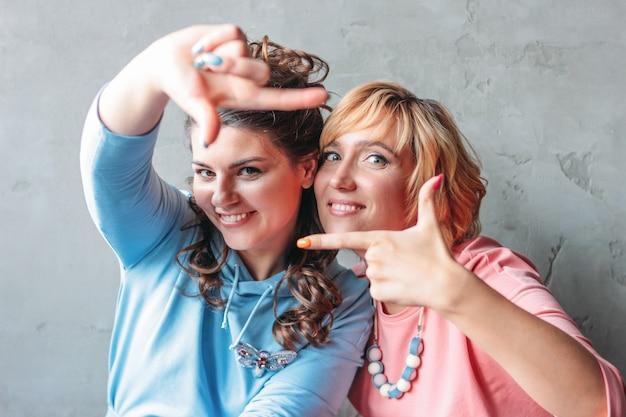 Due belle giovani donne felici amici veri in abito casual sedersi vicino al muro di cemento