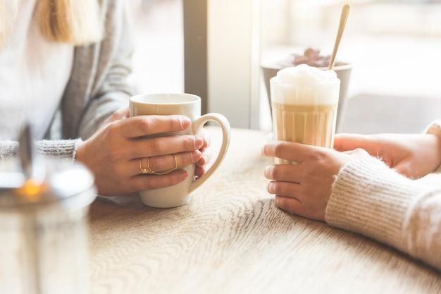 Due belle giovani donne in un caffè, dettaglio