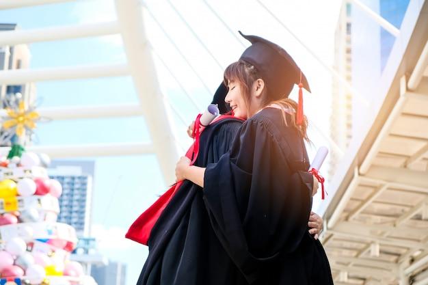 Due belle ragazze asiatiche abbracciano la cerimonia di laurea